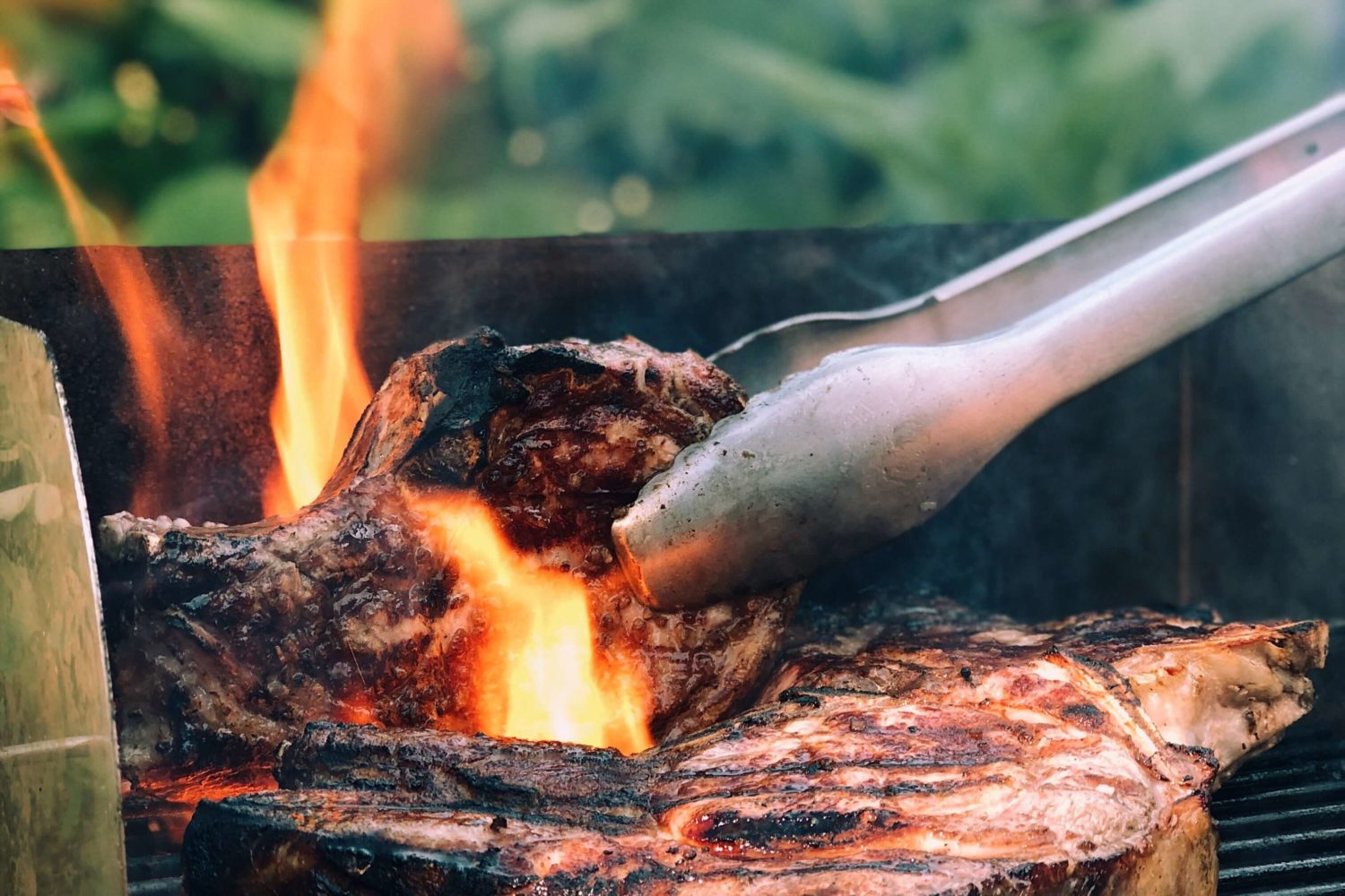 Steaks on a grill being turned with tongs and flames around one steak