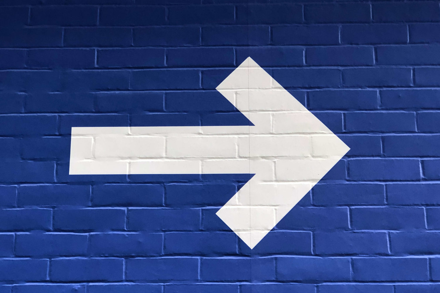 white arrow pointing to the right on blue brick background