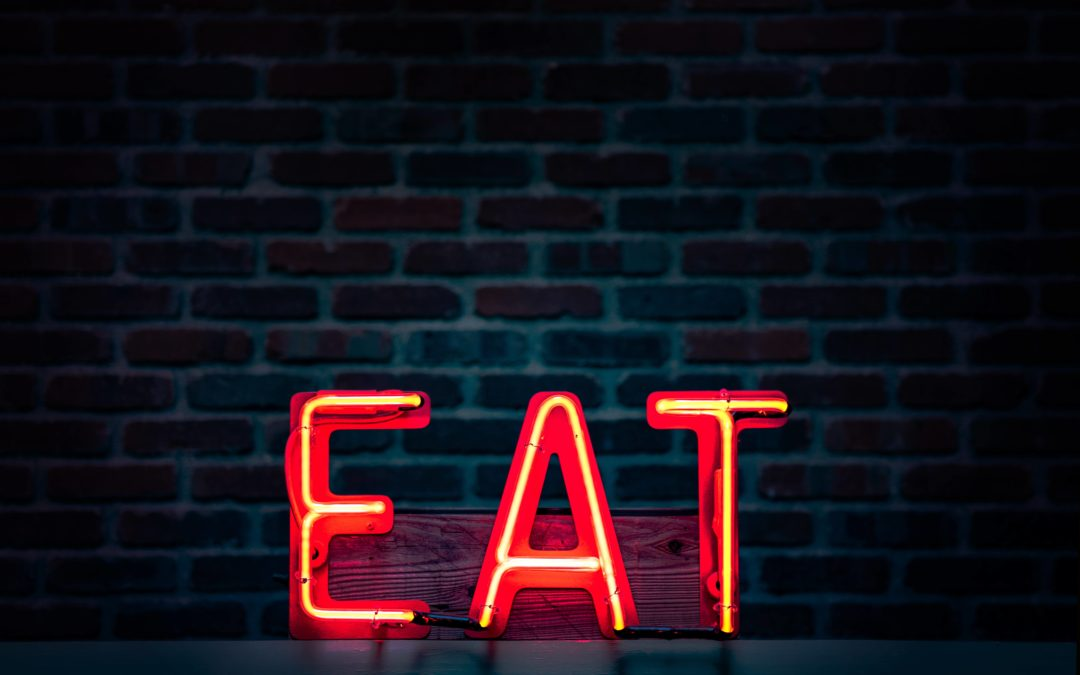 Red neon sign saying EAT on black brick background